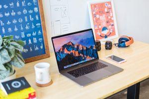 desk with laptop headphones